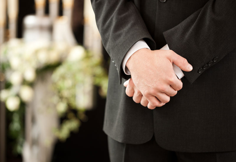 Funeral director with hands crossed